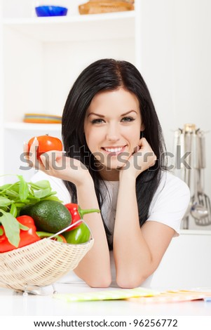 portrait of beautiful woman hold tomato in the kitchen, looking at camera happy smile