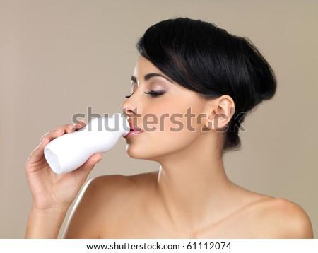 Portrait of beautiful woman, holding bottle of milk