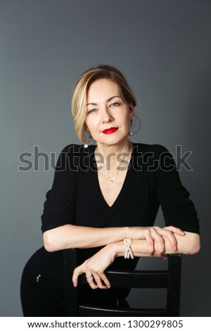 Portrait of beautiful woman in a black dress against grey background Сток-фото ©
