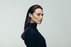 Portrait of beautiful woman in black top wearing earphones staring at camera. Studio shot of young beautiful woman as secret agent against grey background.