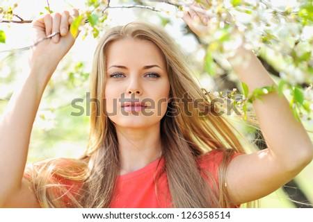 Portrait of beautiful woman in blooming tree in spring