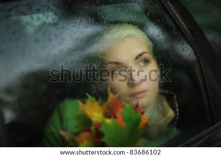 Portrait of beautiful woman in car looking out through wet glass. Closeup.