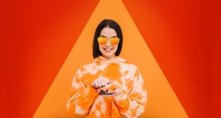 Portrait of beautiful woman in heart-shaped sunglasses. Pretty girl in hoody with smartphone in hands addicted to social media. Bright geometric trendy background. Free space for text. Trends 2020.