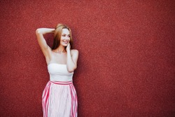 Portrait of beautiful woman in red dress, smiling. Casual lifestyle photo.