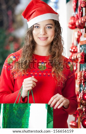 Portrait of beautiful woman in Santa hat carrying shopping bag at store