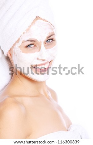 Portrait of Beautiful woman in towel with facial mask over white background