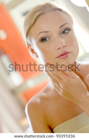 Portrait of beautiful woman looking at a mirror