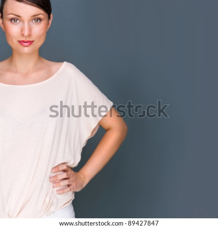 Portrait of beautiful woman looking at camera and holding hands on her waist, she is isolated on grey