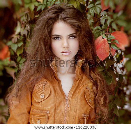 Portrait of beautiful woman model with fresh daily makeup and curly brown hair style.