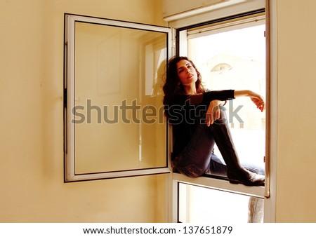Portrait of beautiful woman near the window - stock photo