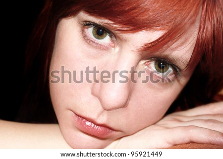 Portrait of beautiful woman on black background with sad expression on her face