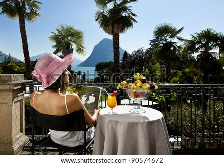 portrait of beautiful woman on the terrace of prestigious hotel