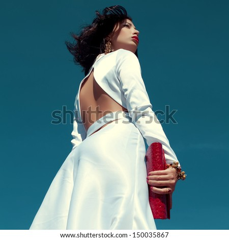 Portrait of beautiful woman posing in elegant white atlas cocktail dress with red leather clutch in her hands over blue sky background. Luxurious golden accessories (bracelet, earrings). Outdoor shot