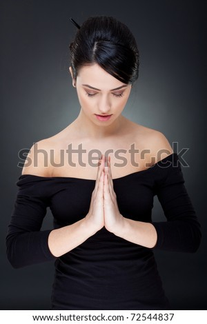 Portrait of beautiful woman praying on a dark background