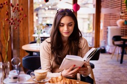 Portrait of beautiful woman reading a book while relaxing in the cafe.