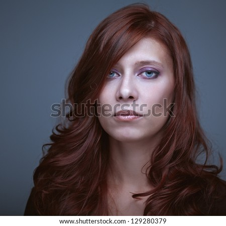 portrait of beautiful woman redhair on gray