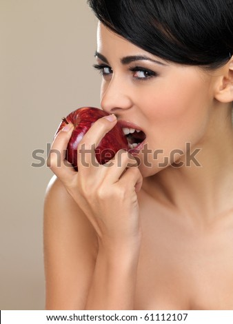 Portrait of beautiful woman, she bites red apple
