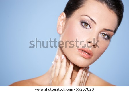 Portrait of beautiful woman she is doing neck massage, isolated on blue