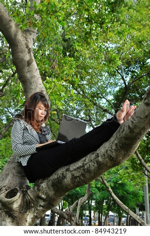 Portrait of beautiful woman sitting on the tree and playing laptop
