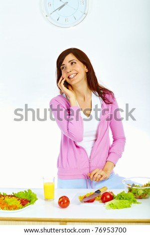 Portrait of beautiful woman standing in kitchen and talking on the mobile phone