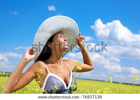 Portrait of beautiful woman standing in the middle of meadow and looking upwards with smile