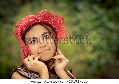 Portrait of beautiful woman standing in the middle of the forrest and holding her hat down with smile
