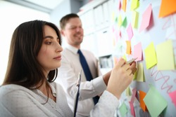 Portrait of beautiful woman sticking colourful notes on board at workplace. Co-workers making biz remarks. Business people preparing presentation. Business concept