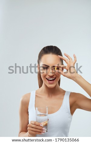 Portrait of beautiful woman taking vitamin pill with glass of fresh water indoors. Smiling girl taking omega 3 fish oil capsule, vitamin supplement. Diet nutrition concept