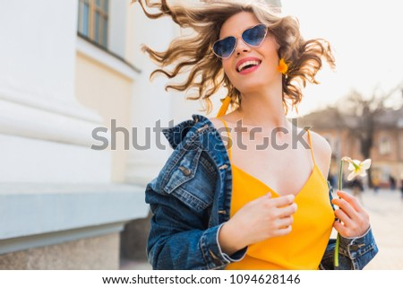 portrait of beautiful woman waving hair smiling, stylish apparel, wearing denim jacket and yellow top, fashion trend, summer style, happy positive mood, sunny day, sunrise, emotional, cheerful