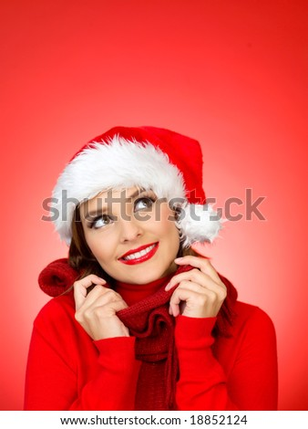 Portrait of beautiful woman wearing santa claus hat on red background