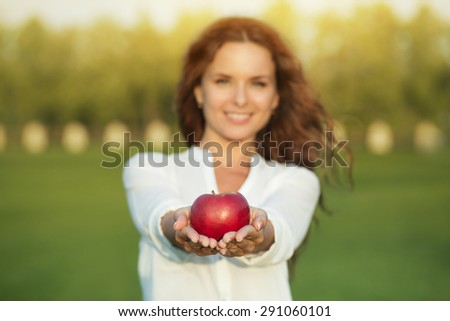 Portrait of beautiful woman with apple. Girl presenting red apple in front of her.