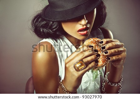 Portrait of beautiful woman with burger on grey background