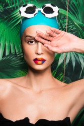 Portrait of beautiful woman with colorful make up, beauty magazine editorial ready, Caucasian girl, with swimming hat, sunglasses and tropical exotic background