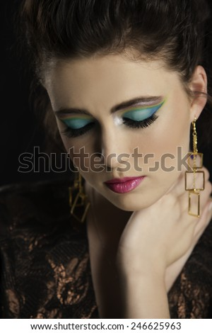 Portrait of beautiful woman with colorful makeup holding her hand to her neck while looking down.