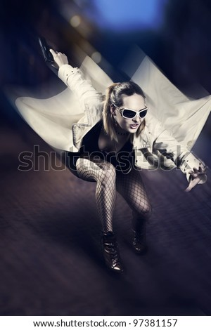 Portrait of beautiful woman with gun in white raincoat and designer sun glasses jumping on night  street. Motion