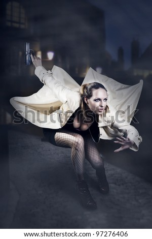 Portrait of beautiful woman with gun in white raincoat jumping on night european street