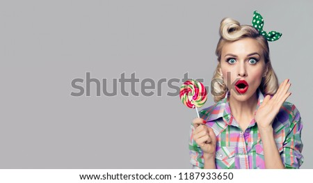 Portrait of beautiful woman with lollipop, dressed in pin-up style. Caucasian blond model posing in retro fashion and vintage concept. Copy space area for advertise, slogan or text message.
