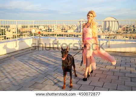 Portrait of beautiful woman with long blond hair in a pink dress with the Doberman on the roof #450072877