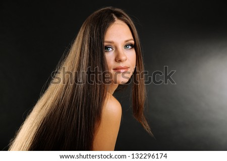 Portrait of beautiful woman with long hair on black background