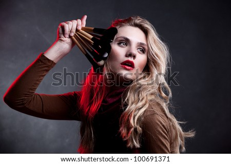 Portrait of beautiful woman with makeup brushes on dark background