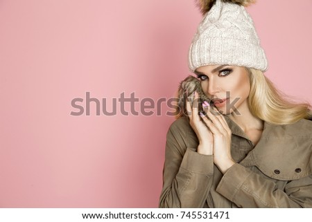 Portrait of beautiful woman with perfect face in winter cap and warm jacket. The model presents winter clothing. #745531471