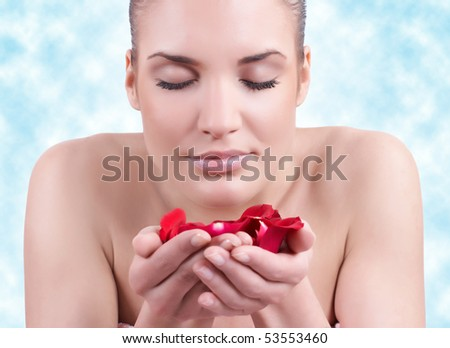 Portrait of beautiful woman with petals in hand.