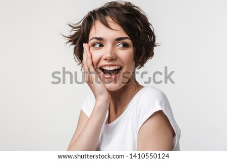 Portrait of beautiful woman with short brown hair in basic t-shirt smiling and touching her face with hand isolated over white background