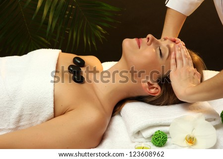 Portrait of beautiful woman with spa stones taking head massage