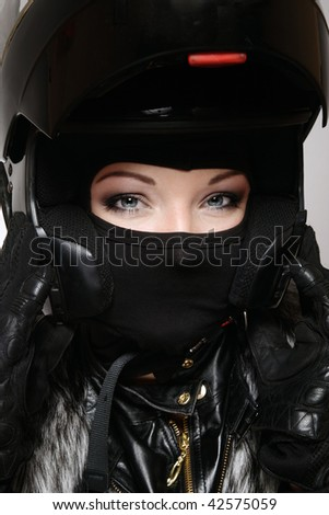 Portrait of beautiful woman with stylish makeup in black biker helmet, mask and gloves