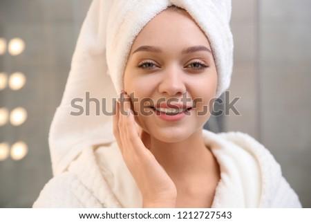 Portrait of beautiful woman with towel on head in bathroom #1212727543