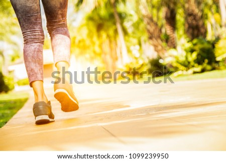 Portrait of beautiful Women running exercising in the park on green tree and green grass background at sunny bright light.