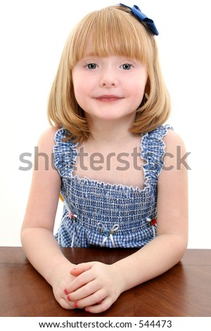 of beautiful 4 year old girl with strawberry blonde hair sitting at