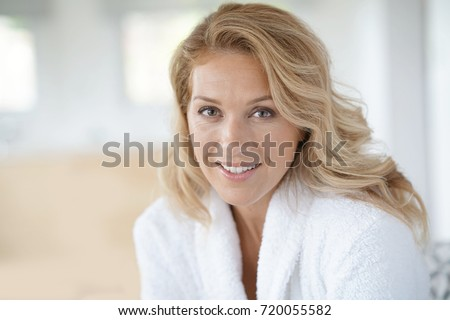 Portrait of beautiful 40-year-old woman relaxing in bathrobe at home #720055582
