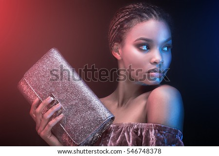 Portrait of beautiful young african girl holding fashionable bag.